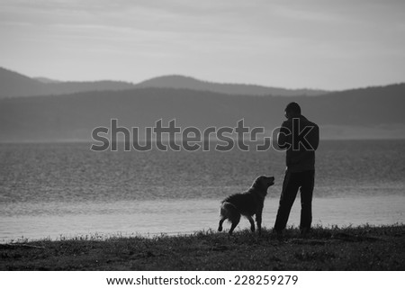 man and dog near high mountain lake in sunset time, black and white landscape  - stock photo