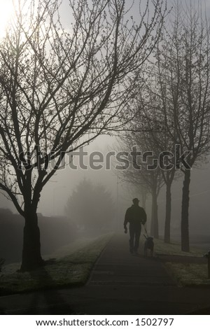 Man and dog on a morning stroll through the lifting fog. - stock photo