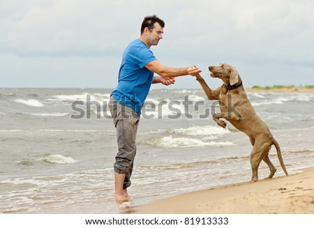 Man and dog on seacoast - stock photo