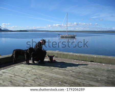 Man and dog on wharf - stock photo