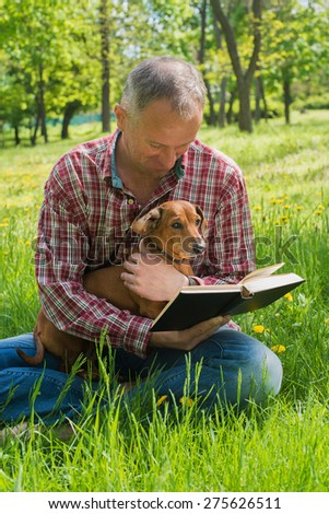 Man and dog read the book - stock photo