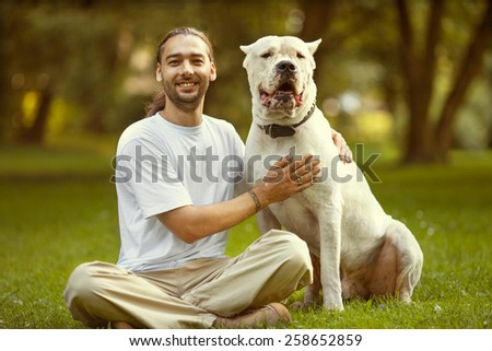 Man and dog walk in the park.  - stock photo