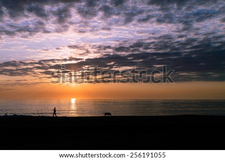 Man and Dog Walking at Sunrise Avon, North Carolina - stock photo