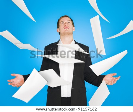 Man and flying papers on blue background - stock photo