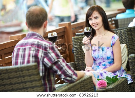 Man and girl drinking wine at street cafe on a date with flover on table - stock photo