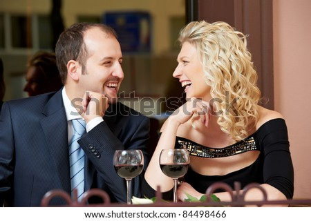 Man and girl drinking wine at street cafe on a date with flower on table - stock photo