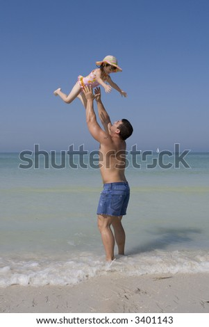 Man and girl having fun on a beach. Blue sky in the background. - stock photo