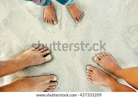 Man and girl legs and a child on the sand near the sea - stock photo