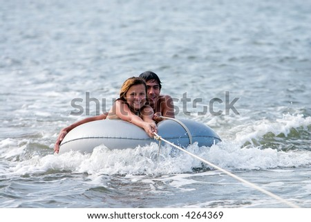 Man and girl on tube in water being towed by boat. - stock photo