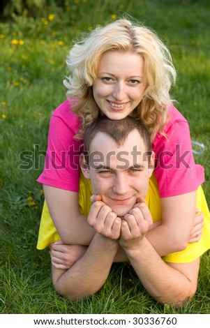 man and girl resting on the green grass