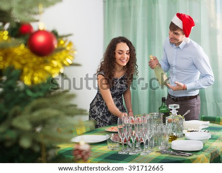 Man and girl serving Christmas table for  guests in home