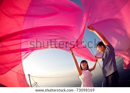 man and girl under the sail - stock photo