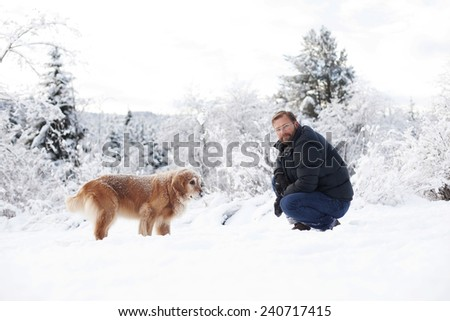man and golden retriever in the snow winter fun  - stock photo