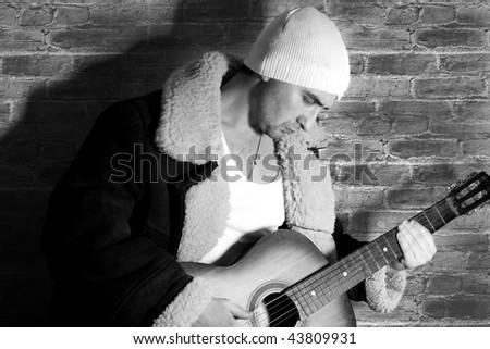 man and guitar at brick background - stock photo
