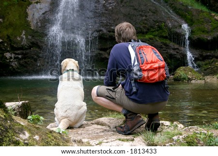 Man and his dog enjoying the beautiful view - stock photo