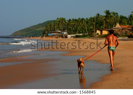 man and his dog on the beach, goa India. - stock photo