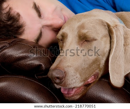 Man and his dog sleeping together on the couch - stock photo