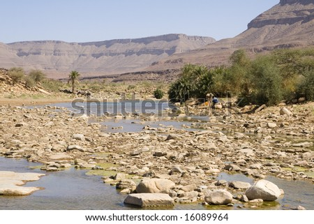 Man and his donkey on the river surrounded by hills
