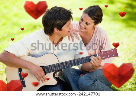 Man and his friend look at each other while he is playing the guitar against hearts - stock photo