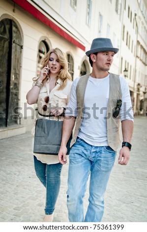 Man and his girlfriend goes shopping in the city - stock photo
