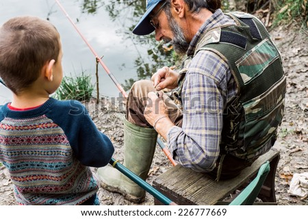 Man and his grandson fishing - stock photo