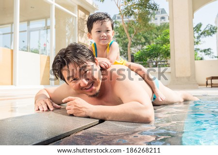 Man and his little son relaxing at the poolside - stock photo