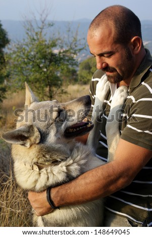 Man and his purebred Czechoslovakian wolf dog - stock photo