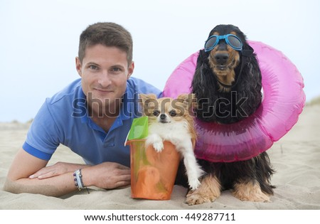 man and his two dogs lying down on the beach