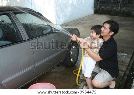 Man and kid washing car in a sunny afternoon happily