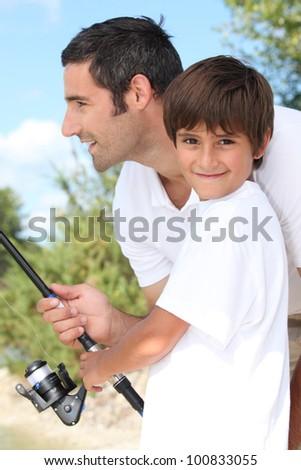 Man and little boy fishing - stock photo