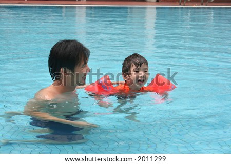 Man and little boy having fun in the pool - stock photo