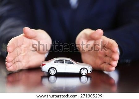 Man and model of car on wooden table, closeup - stock photo