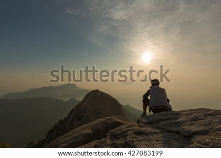 Man and nature. Tourist looking to Sunrise from higher point of mountains over beautiful valley with during calm summer evening