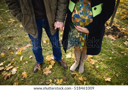 man and pregnant woman on the ninth month or husband and wife walking in the autumn park on the green grass meadows and yellow leaf rot