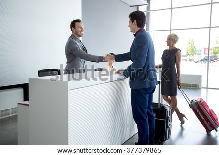 Man and receptionist handshake at reception hall  - stock photo