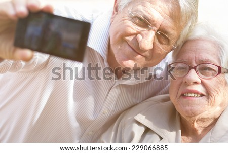 Man and senior woman taking selfie with retro filter effect - stock photo