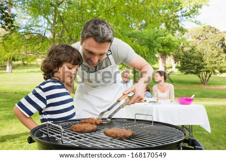 Man and son barbecuing with family in the background at park - stock photo
