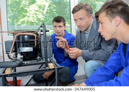 Man and students looking at an invention - stock photo