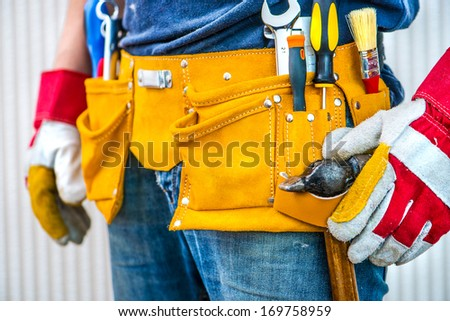 man and tools in leathern belt - stock photo