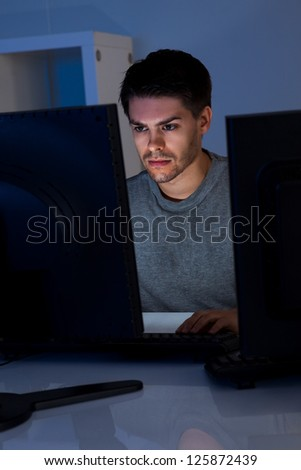 Man and two computers looking at screen in the dark - stock photo