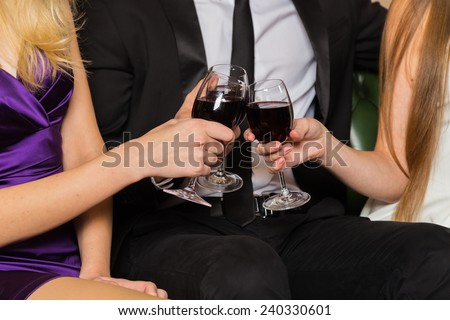 Man and two  woman at meeting are drinking wine. Group of happy young people drink wine. The relationship between a man and a woman - a love triangle, jealousy, betrayal, love, booze. - stock photo
