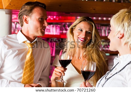 Man and two women in a hotel bar in the evening having glasses of red wine and probably a little flirt - stock photo