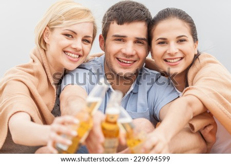 Man and two women relaxing on beach with beer. Happy friends drinking together on beach with focus on friends