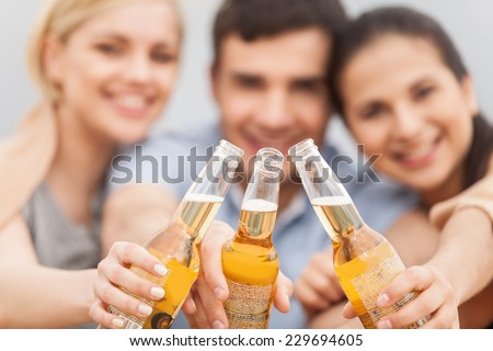 Man and two women relaxing on beach with beer. Happy friends drinking together on beach with focus on bottle - stock photo