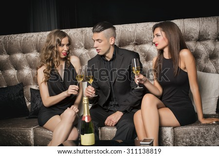 Man and two young woman drinking champagne, celebrating - stock photo