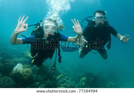 man and wife scuba dive together - stock photo