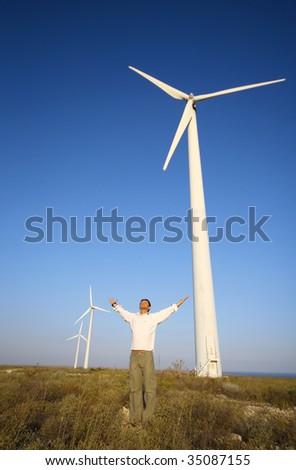 man and wind turbines under blue sky - stock photo