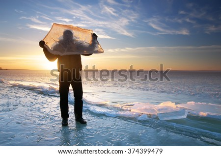 Man and winter ice block in hand.  - stock photo