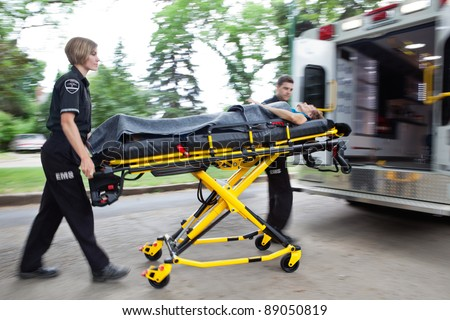 Man and woman ambulance team rushing a senior woman into the vehicle - stock photo