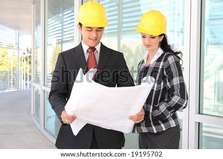 Man and woman architects on building construction site working - stock photo
